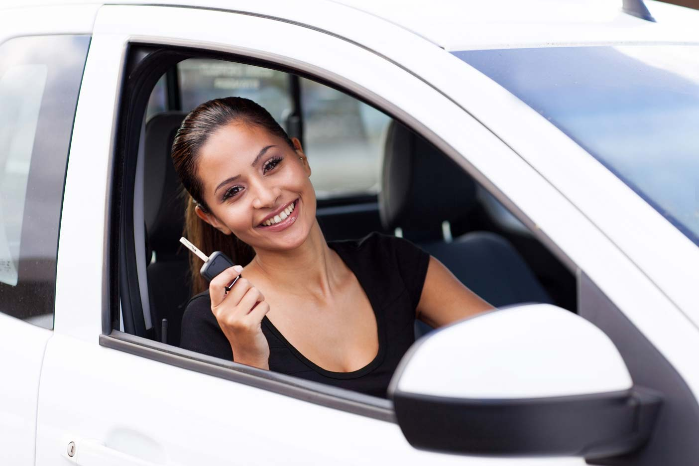 Happy woman in driving seat of car